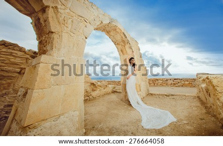 beautiful young Woman standing wearing White and Gold Greek Costume inside ancient ruins. - stock photo