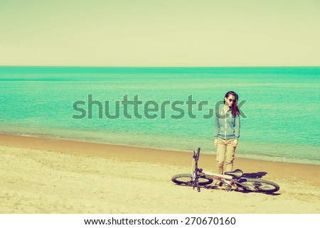 Beautiful young woman standing with a bicycle on beach. Image with instagram effect - stock photo