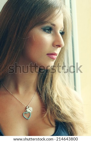 beautiful young woman stands near the window - stock photo