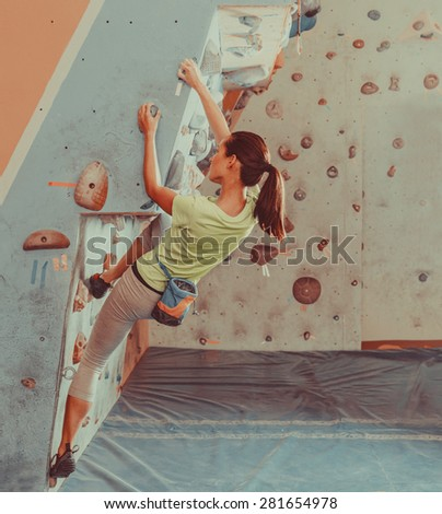 Beautiful young woman starts to climbing on practical wall indoor, bouldering - stock photo