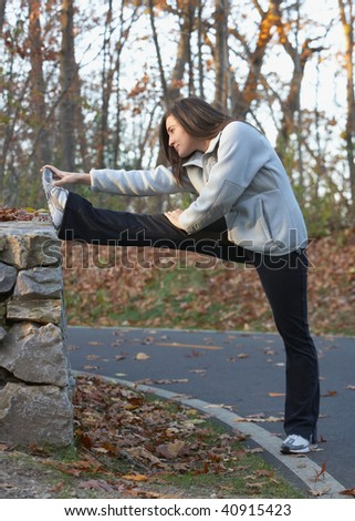 Beautiful young woman stretching hamstring outdoors in park - stock photo