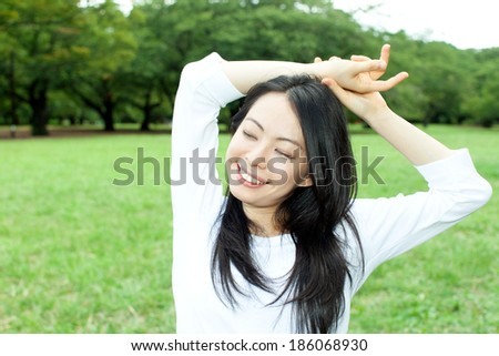 Beautiful young woman stretching in the grass field