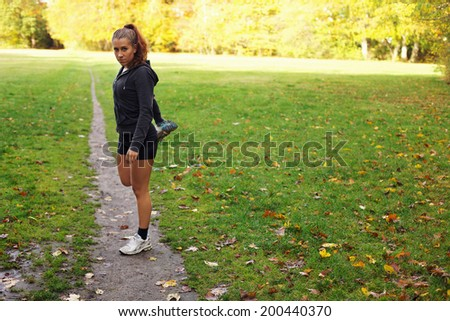 Beautiful young woman stretching leg muscles during workout in park. Pretty young caucasian female runner warming up for exercise outdoors. Confident fitness model in city park.