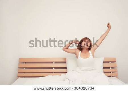 Beautiful young woman stretching on bed after wake up in the morning - stock photo