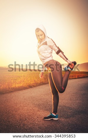 Beautiful young woman stretching outdoors before running training