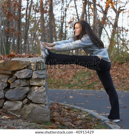 Beautiful young woman stretching outdoors in autumn park - stock photo