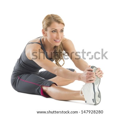 Beautiful young woman stretching to touch her toes isolated against white background - stock photo