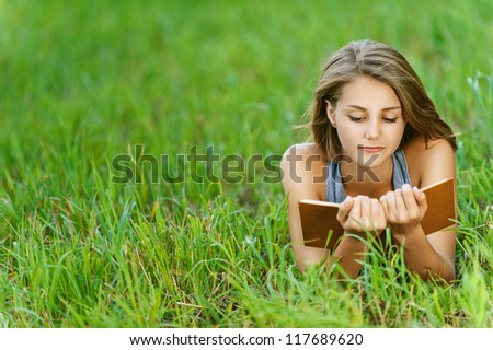 Beautiful young woman-student reading book on grass, against background of summer green park.