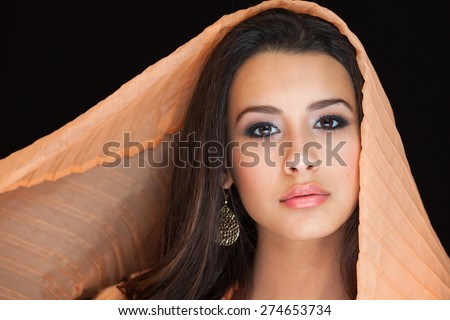 Beautiful young woman studio portrait covered by a colorful veil on a black background. - stock photo