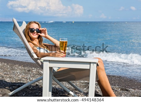 Beautiful young woman sunbathing on a lounger on the beach