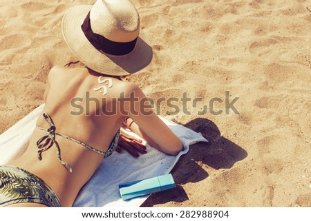 beautiful young woman sunbathing on the beach with a sun cream shape on her shoulder