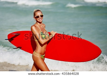 Beautiful young woman surfer girl in bikini with surfboard on the beach - stock photo