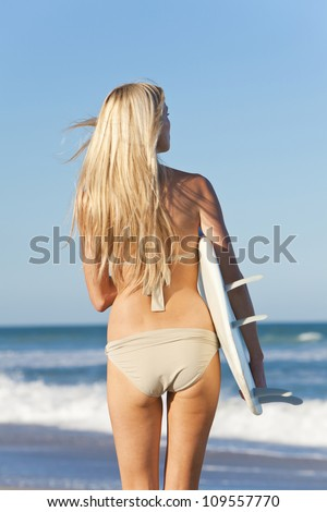 Beautiful young woman surfer girl in bikini with white surfboard at a beach - stock photo