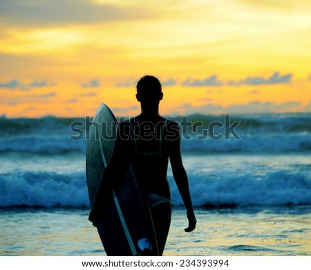 Beautiful young woman surfer with board on the beach - stock photo