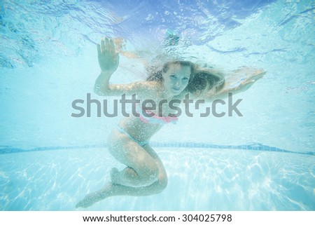 Beautiful young woman swimming underwater in pool - stock photo