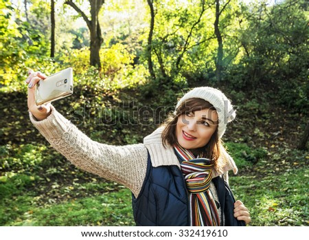 Beautiful young woman take the selfie photo in autumn nature. Beauty and fashion.