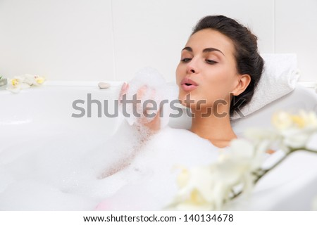 beautiful young woman takes bubble bath - stock photo