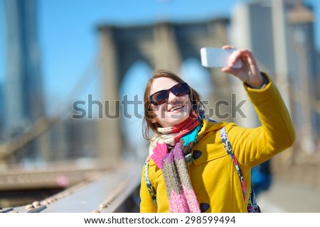 Beautiful young woman taking a selfie with her smartphone on Brooklyn Bridge, New York, at sunny spring day - stock photo