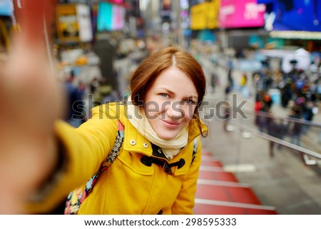 Beautiful young woman taking a selfie with her smartphone on Times Square, New York