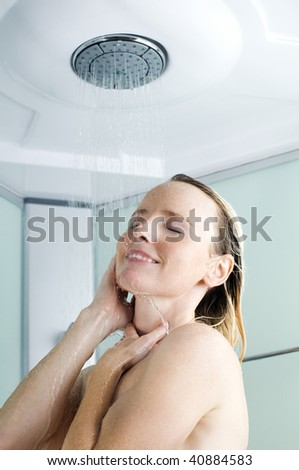 Beautiful young woman taking a shower close up - stock photo