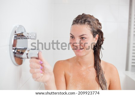 Beautiful young woman taking a shower/hot bath tub and washing hair - stock photo