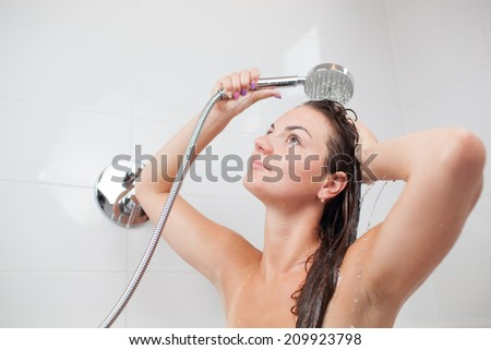 Beautiful young woman taking a shower/hot bath tub and washing hair