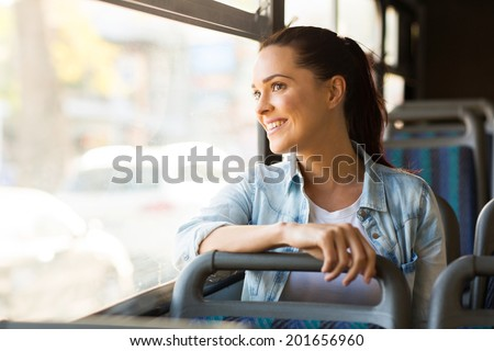 beautiful young woman taking bus to work - stock photo