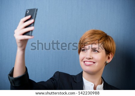 beautiful young woman taking self portrait with her smart phone - stock photo