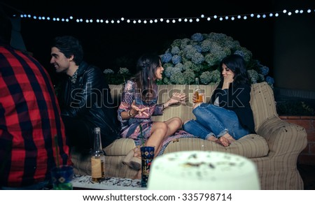 Beautiful young woman talking about her problems to bored female friend in a outdoors party. Friendship and celebrations concept. - stock photo
