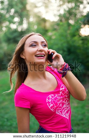 Beautiful young woman talking on a phone in city park. - stock photo