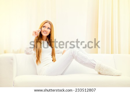 Beautiful young woman talking on the phone at home sitting on the couch.