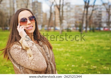 Beautiful young woman talking on the smart phone at park. Shallow depth of field. - stock photo