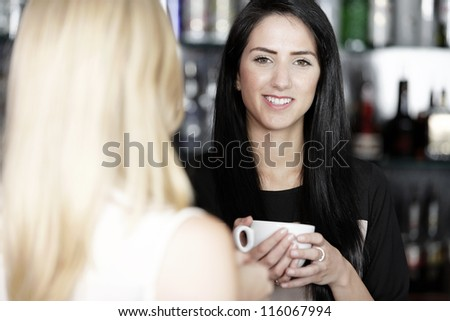 Beautiful young woman talking over coffee at a wine bar. - stock photo