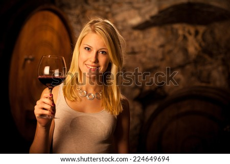 Beautiful young woman tasting red wine in a wine cellar - stock photo