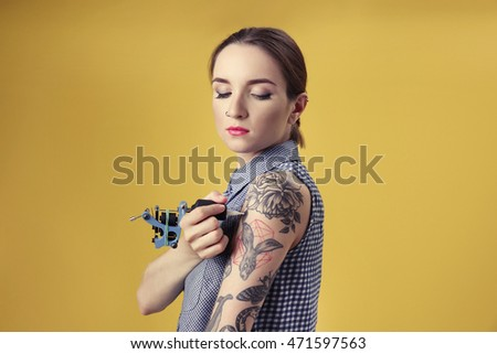 Beautiful young woman tattooing herself and posing on yellow background