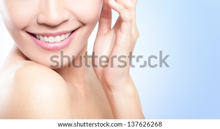 Beautiful young woman teeth close up with copy space on the right side. Isolated over blue background, asian beauty model - stock photo