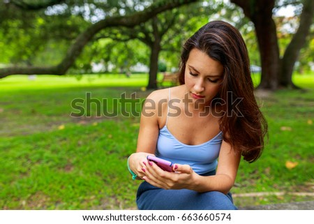Beautiful young woman texting outdoor portrait in a park setting.