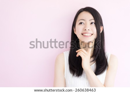 beautiful young woman thinking against pink background