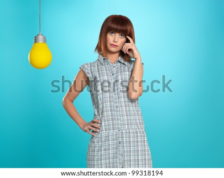 beautiful, young woman thinking of an idea, with a big, yellow lightbulb, on blue background
