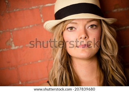 Beautiful Young Woman - This is a shot of a beautiful young woman wearing a fedora against a brick wall. - stock photo