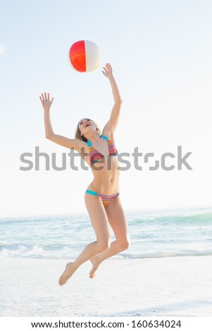 Beautiful young woman throwing a beach ball while jumping on the beach