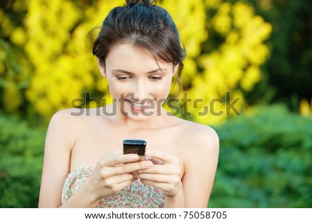 Beautiful young woman to read SMS from your mobile phone on natural background - stock photo