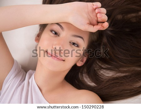 Beautiful young woman. Top view of attractive young woman lying on back and holding her hand on forehead