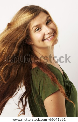 Beautiful young woman tossing her hair - stock photo