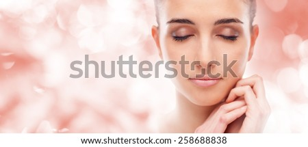 Beautiful young woman touching her radiant face skin with eyes closed  - stock photo