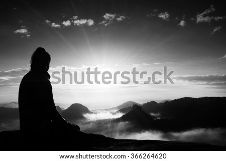 Beautiful  young woman tourist enjoy daybreak on the sharp corner of sandstone rock and watch over valley to Sun. Black and white photo - stock photo