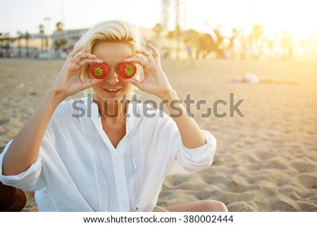 Beautiful young woman tourist holding two ripe red strawberries against her eyes while enjoying rest on the sea beach, charming female in good mood having fun during summer vacation outside - stock photo