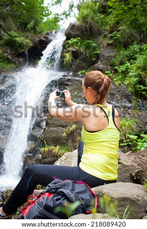 Beautiful young woman tourist sitting on a rock and taking a photo of waterfall (colorful image)