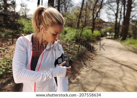 Beautiful young woman training outdoors while using a smartphone to monitor her progress. Caucasian female runner in forest. - stock photo