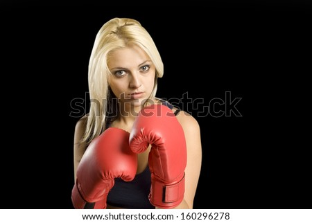 Beautiful young woman training with boxing gloves on blackboard background - stock photo